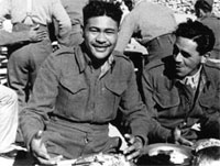 A big smile from W Eratara as he sits down to Christmas Dinner, Maadi Camp, Egypt, 1943. Image courtesy of Army Museum
